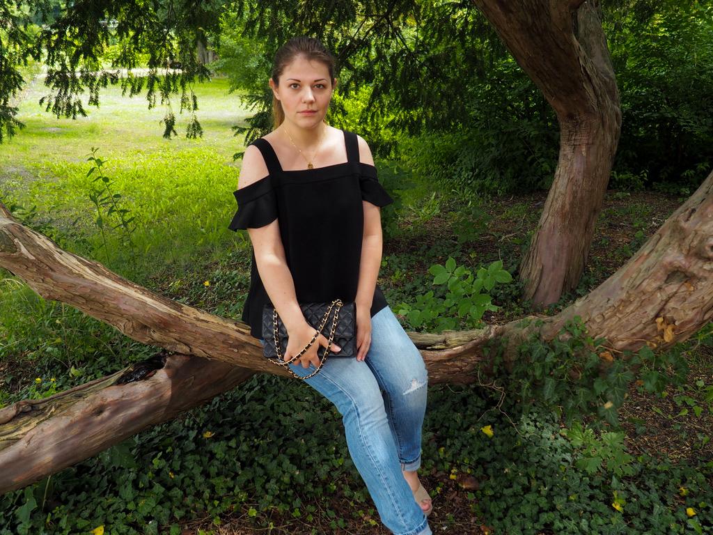 Mädchen sitzt zwischen Bäumen